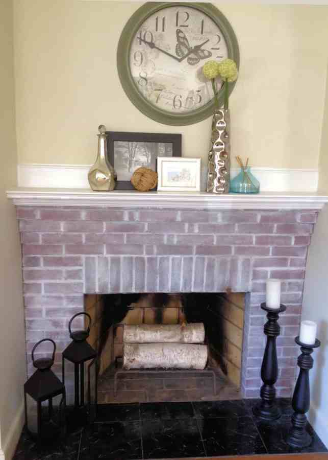 A painted brick fireplace using a whitewash of white paint