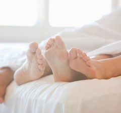 Close up of couple's feet in bed