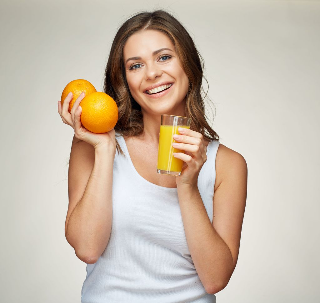 healthy lifestyle portrait of smiling sporty woman holding vitamin set with orange juice and fruit. studio isolated.
