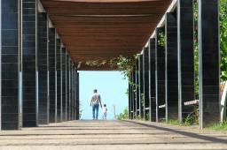 Man and Child Walking Under Bridge