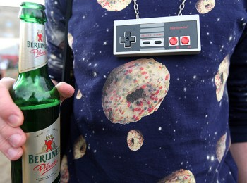 An attendee wearing a 1980s Nintendo controller as a necklace