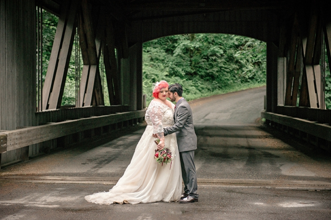 plus size bride holding flowers, groom on a wooden bridge