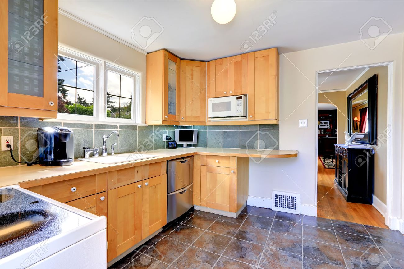 34354486 Modern light tone kitchen cabinets with steel dishwasher Kitchen with brown tile floor and tile back Stock Photo