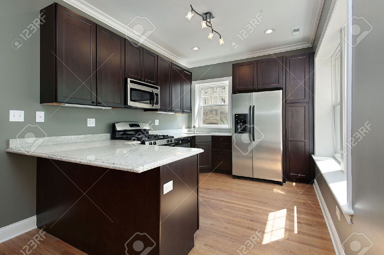photo kitchen in remodeled condominium unit mahogany cabinetry stock kitchen cabinets Kitchen in remodeled condominium unit mahogany cabinetry Stock Photo