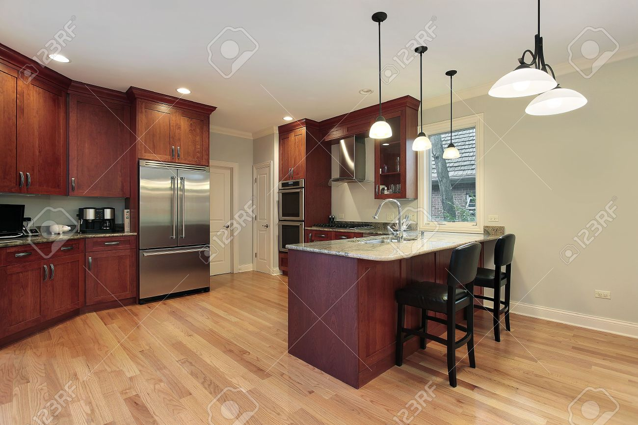 6740544 Kitchen in luxury home with cherry wood cabinetry Stock Photo kitchen island
