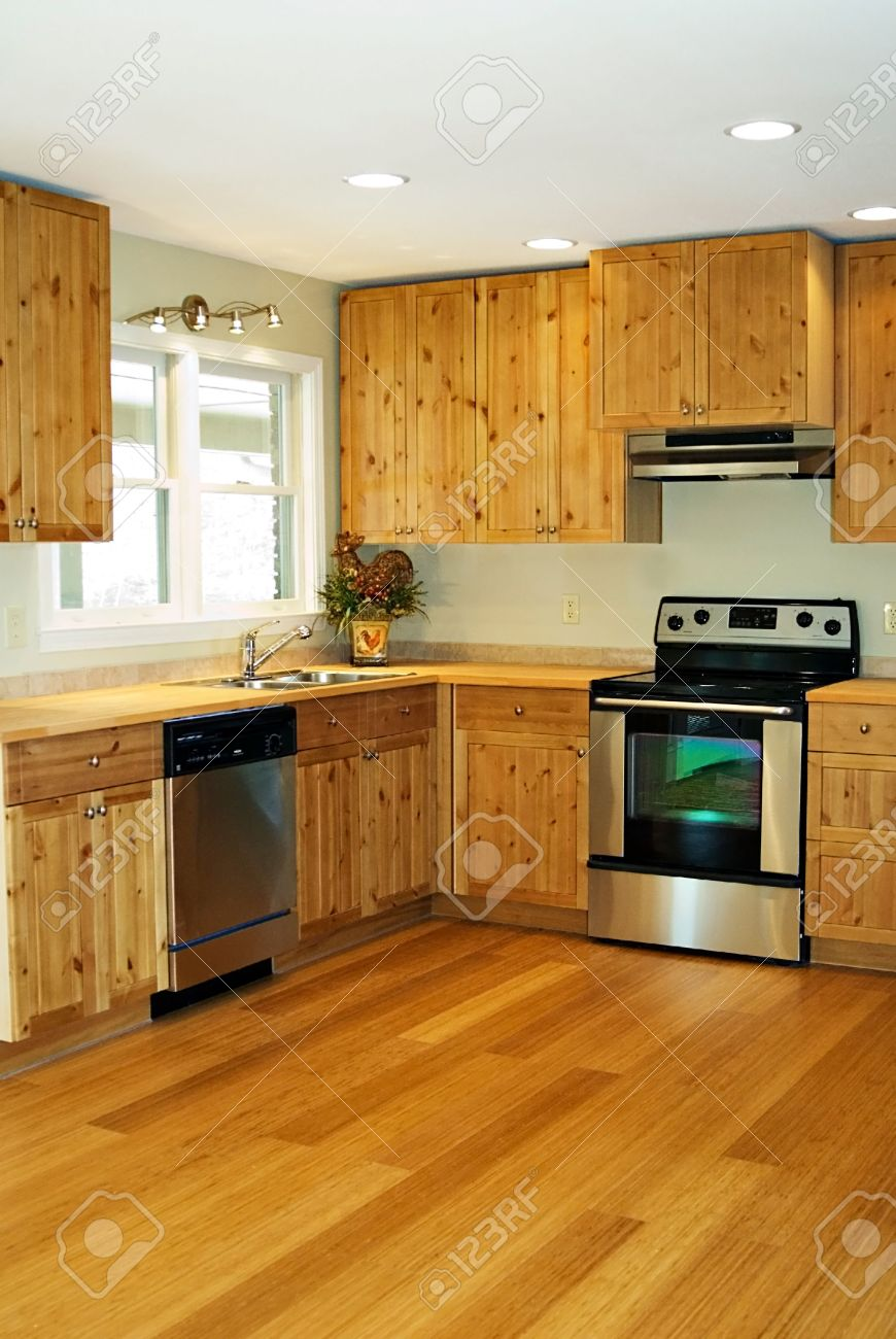 7899704 A small new kitchen with bamboo flooring and pine cabinets  Stock Photo