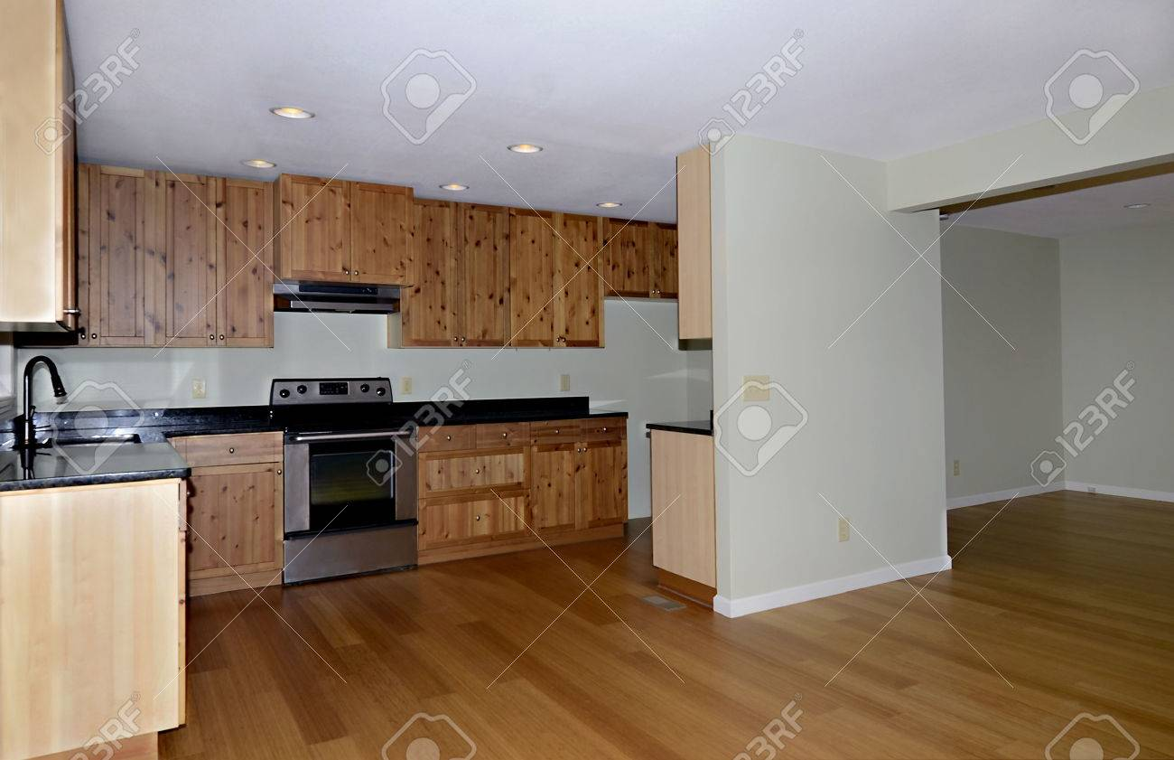 28621948 View of a kitchen and dining area with knotty pine cabinets and bamboo floors Sun is shining through Stock Photo