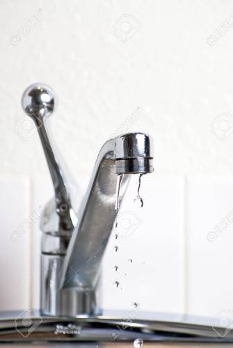 5767542 Dripping faucet leaking into the sink in the kitchen Stock Photo