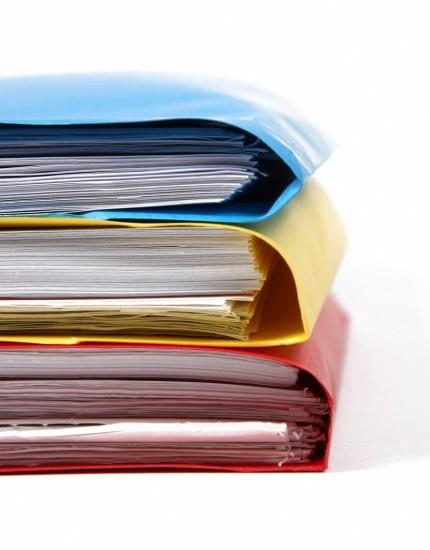 in stapel von ordnern und papph¸llen verschiedener farben.  die ordner sind gef¸llt und ¸berandergestapelt. ein bild f¸r b¸roleben und studium.