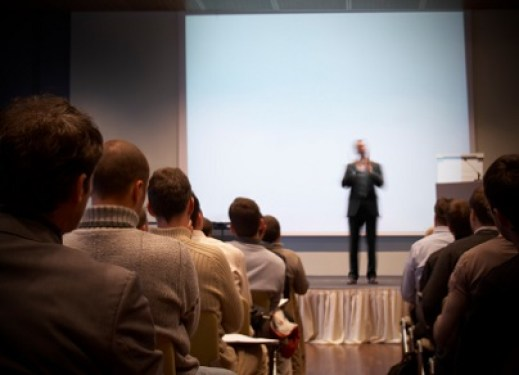 Business conference with lecturer and projection. Lecturer is blurred.