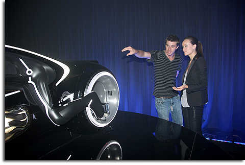 Garrett Hedlund and Olivia Wilde examine a lightcycle