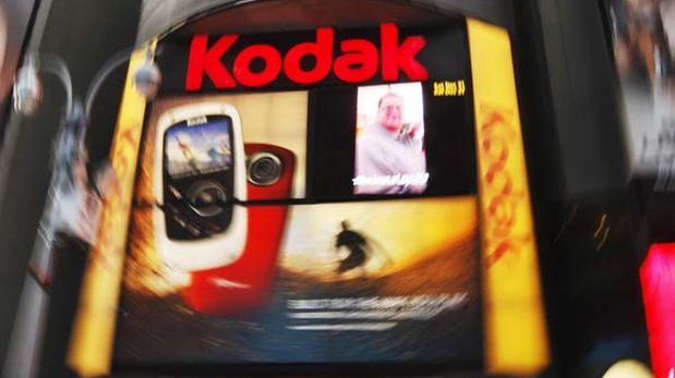 People walk in front of a Kodak screen at Times Square in New York