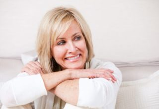 Happy mature woman in her 50s. She is sitting with her arms crossed. Woman is resting her chin on her crossed arms. She is wearing an off white color with the similar off white color in the background. She is smiling and looking of to the side.