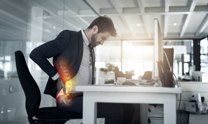 Shot of a businessman suffering from backache while sitting in his office