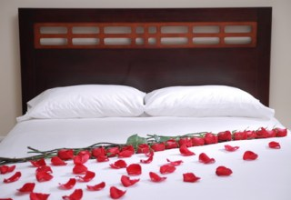 white hotel bed withe roses and petals on it