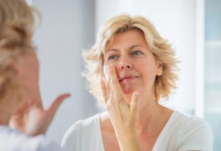 Mid adult woman standing in front of the bathroom mirror and spreading a layer of facial cream on her cheeks