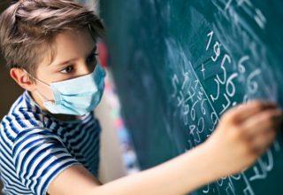 Little boy wearing face mask doing math calculations. Nikon D850