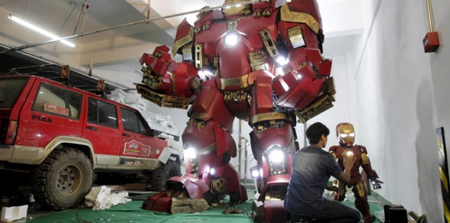 A man works on a small replica of the Iron Man armor next to a h