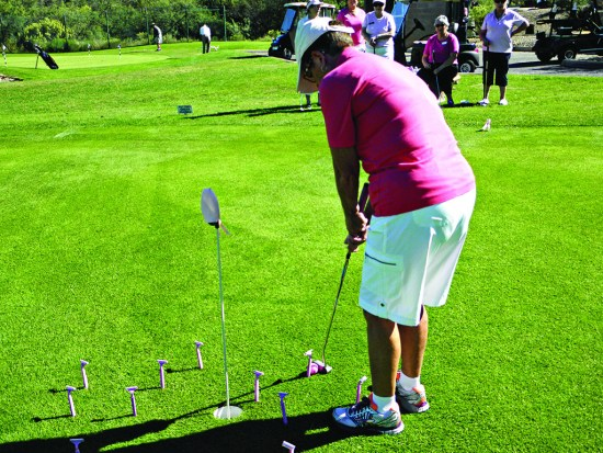 Patti Hall squares up to putt around some disposable razors; photo by Fred Waggoner.