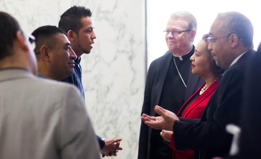Los senadores estatales Marisol Alcántara y José Peralta, y el obispo católico de Albany, Edward B. Scharfenberger, hablan con  trabajadores agrícolas en Albany.