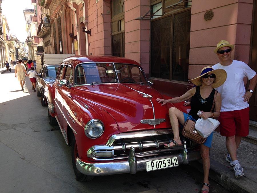 Los turistas posan fascinados al lado de los carros clásicos en La Habana. Foto Roger Rivero