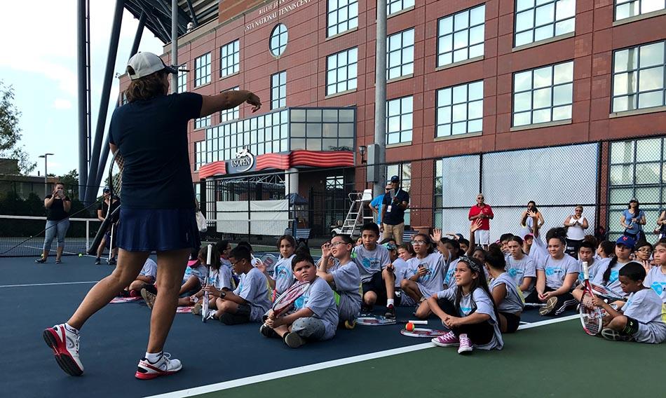 Gigi Fernández hablando con los niños latinos para motivarlos a jugar tenis.