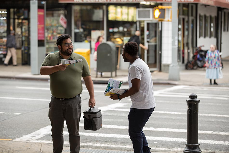 Staffer from de Blasio administration hands out information on tenants rights to New Yorker for Day of Action.
