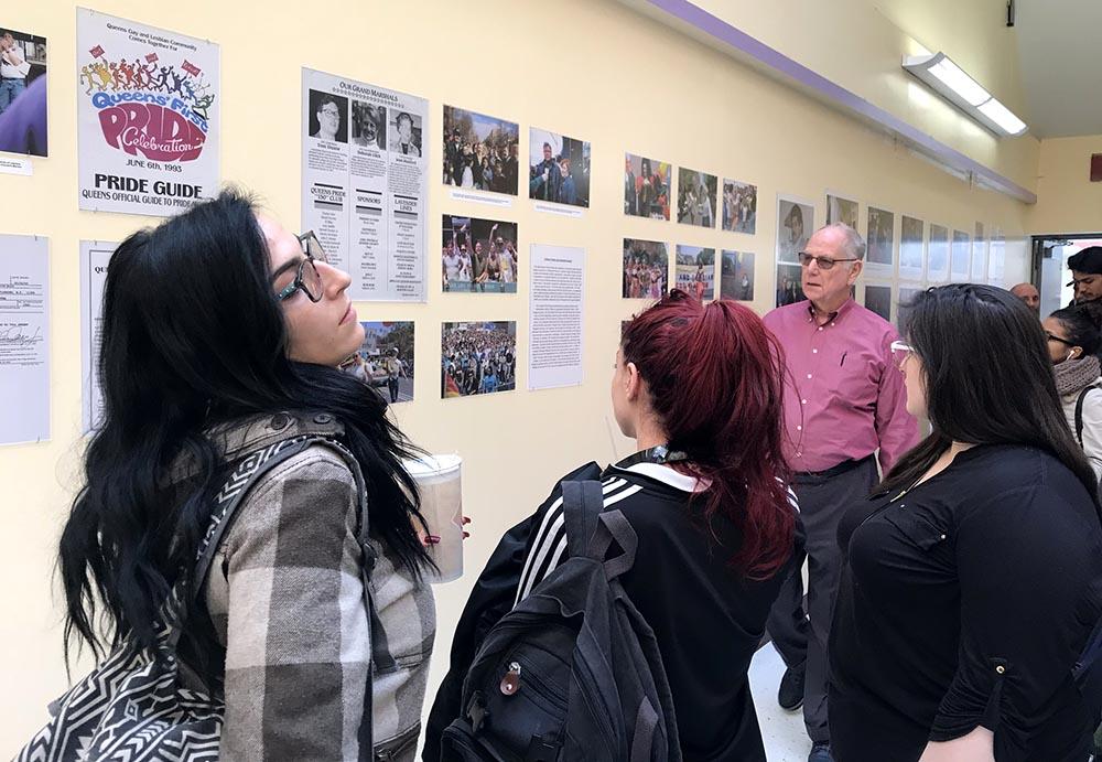 Estudiantes observando la exhibición de fotos del Desfile del Orgullo Gay en Queens.
