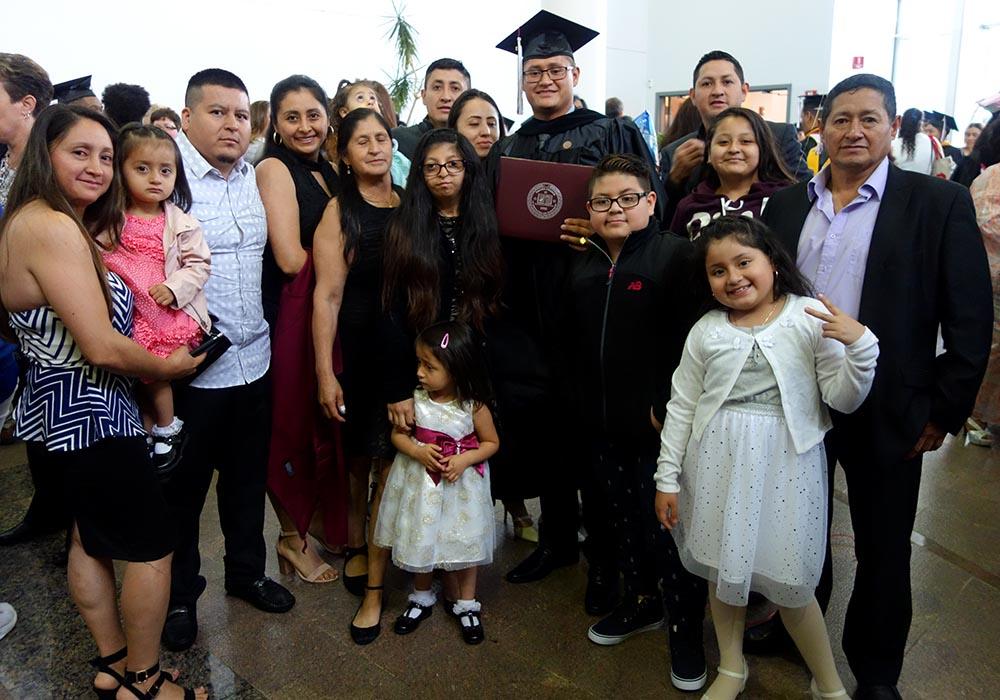 Diego Carpio con toga y birrete y acompañado de su familia en el Vaughn College.