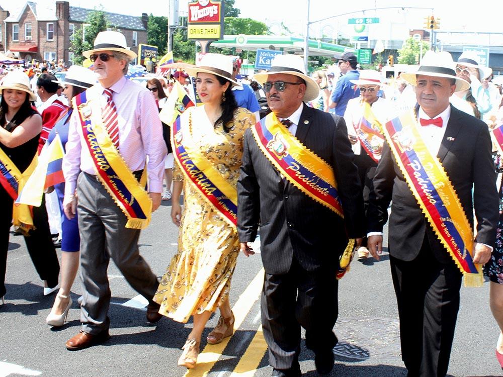Oswaldo Guzmán, de gafas oscuras, desfilando en compañía de representantes del cuerpo consular de Ecuador.