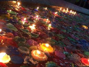 entzuendete Kerzen im Kirchenbrunnen