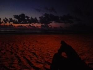 Den Sonnenaufgang am Strand bewundern