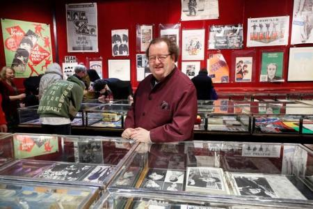 El coleccionista y especialista francés en Los Beatles Jacques Volcouve, uno de los mayores expertos sobre la banda del mundo, posa junto a los más de 15.000 objetos que se subastarán el sábado en París. REUTERS/Charles Platiau