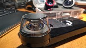 This is a close-up of the Kogeto 360º lens. The reflective surface/dome is on top. The light has to pass through the plastic housing, bounce off the silver dome, through another clear piece of something, THEN into the camera...