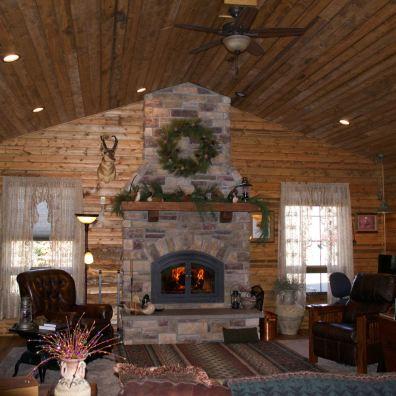 A cozy living room fireplace, surrounded by pine floor, walls and ceiling.