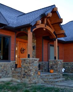 Front entryway with large alder door, custom stonework and timbers.