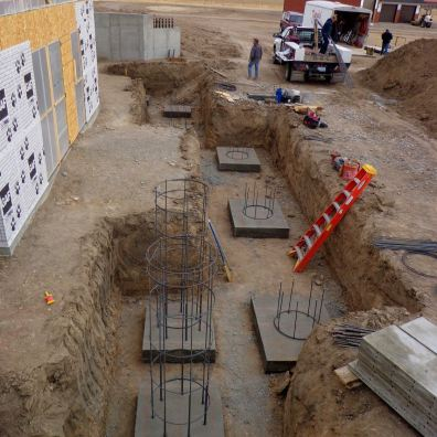 Buried footings and reinforcing steel cages that will become support piers for a large deck.
