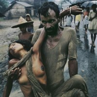 A refugee carrying his cholera-stricken wife away from the fighting during the Bangladesh War, 1971