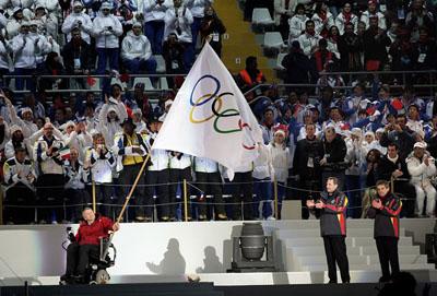 車いすを操作して五輪旗を振る、次期冬壤??輪開催地バンクーバーのサリバン市長(朝日新聞)