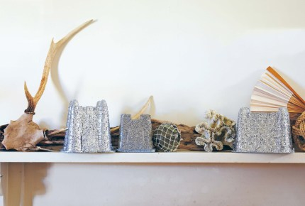 Sand castle buckets painted with silver glitter adorn a mantel.