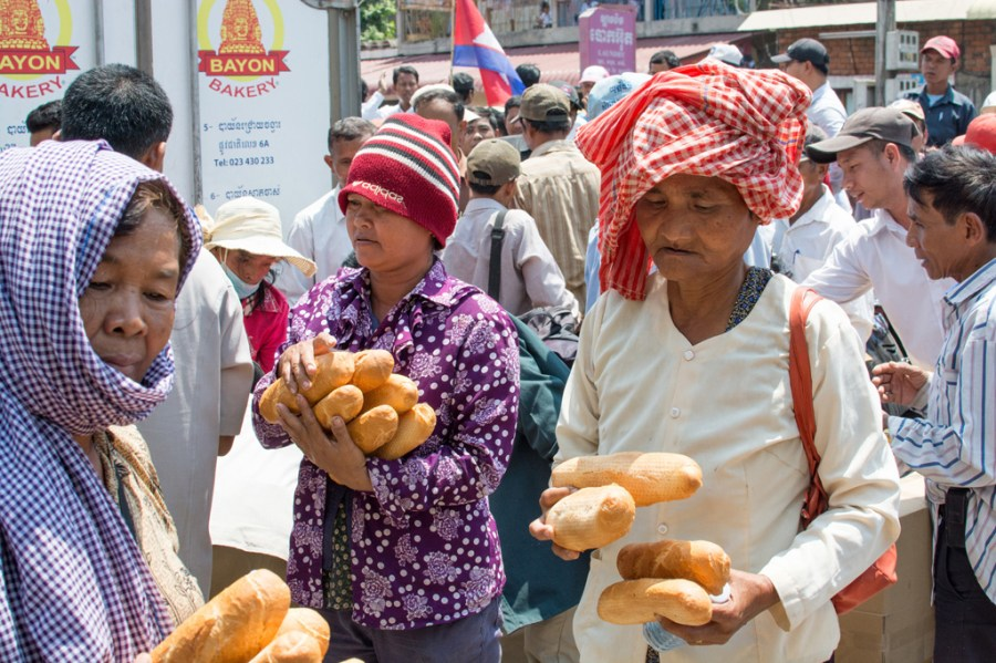 CNRP supporters, and passersby, collect bread provided by the CNRP at a rally outside its headquarters in Phnom Penh. // Alex consiglio