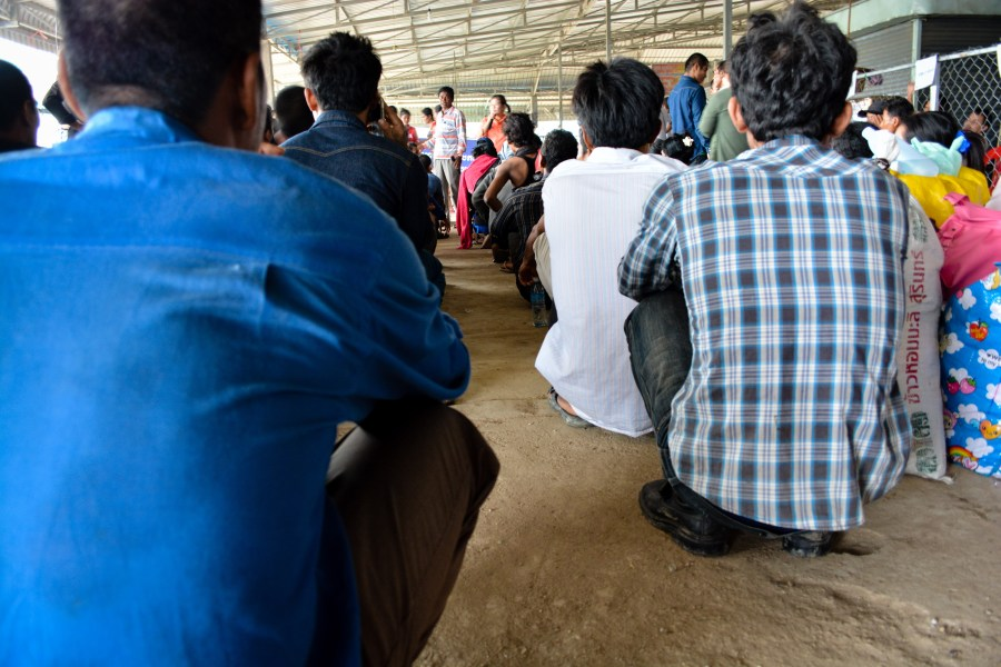 Migrant workers squat to receive instruction on where to board buses to their home provinces. // Alex Consiglio