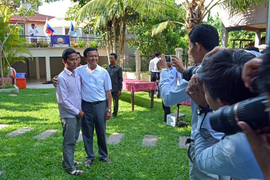 CNRP leader Kem Sokha poses for photos with each of the 23 men convicted with suspended sentences for their roles in early January 2014 protests. (Alex Consiglio/The Cambodia Daily)