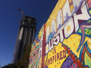 The Market Square Tower, an apartment tower under construction in downtown Houston rises near Treebeard's, a restaurant with a colorful mural. Photo credit: Ralph Bivins. Copyright 2016.