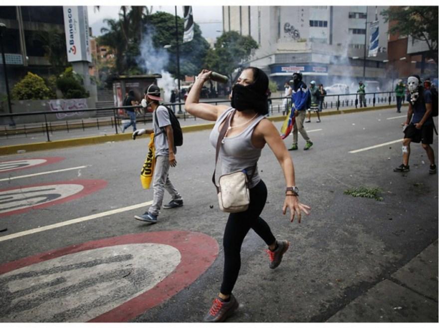 Une jeune femme jette une bouteille en direction des forces de l'ordre, le 20 avril à Caracas.