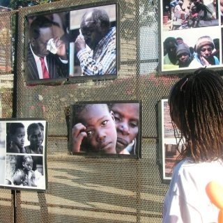 A woman looking at the photos that were exhibited during a past Heal The Nation Exhibition organised by Boniface Mwangi In the streets of Nairobi. [Picture: Carolyne Oyugi]