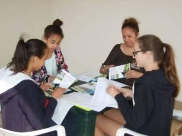 Les filles au collage des étiquettes en présence de l'éducatrice spécialisée
