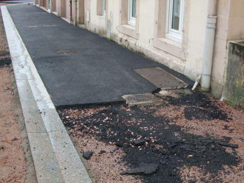 Un caniveau délimite la partie aire de stationnement et la chaussée