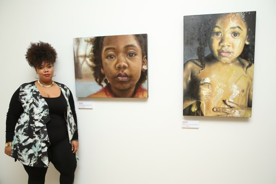 Artist Princess Smith poses with two of her paintings (Photo by Cindy Ord/Getty Images for Canon)