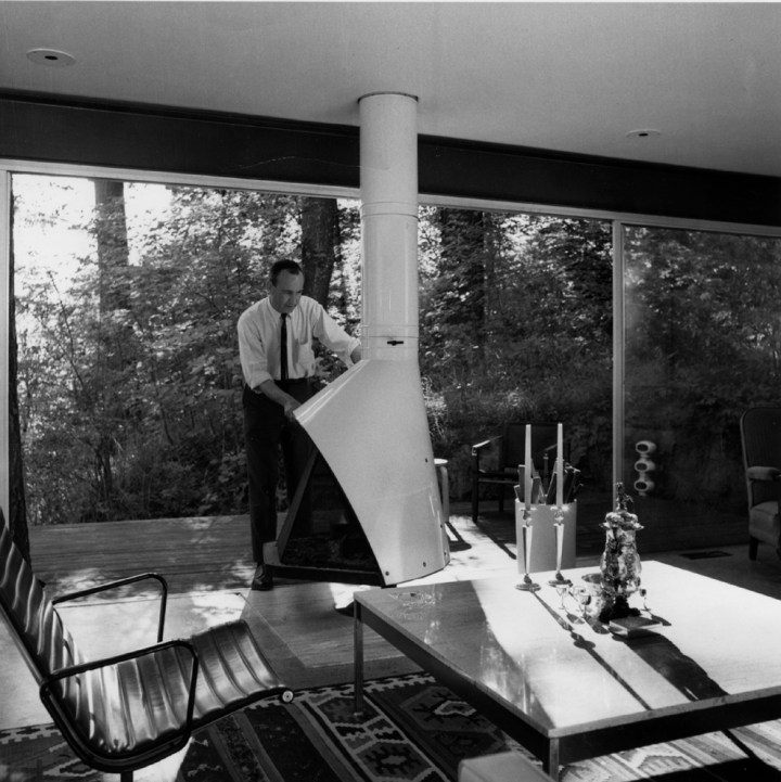 William Fletcher adjusting a fireplace in one of the houses he designed